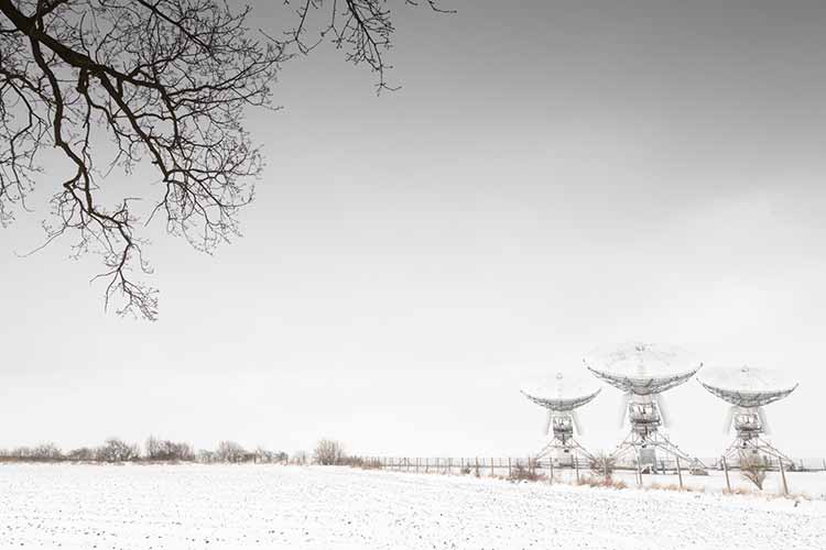 Three radio telescopes in a white field covered in snow, with a bare tree branch in the foreground