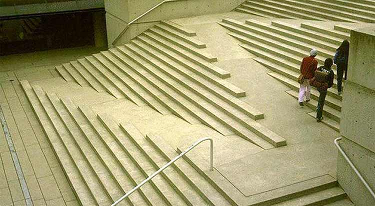 Photograph of people walking up a staircase with an integrated wheelchair access ramp